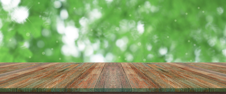 top wooden long table with natural green bokeh abstract background