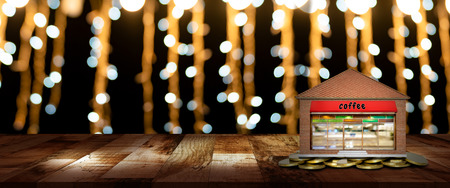 Shops and gold coins on the wooden table with blurred bokeh of night street background