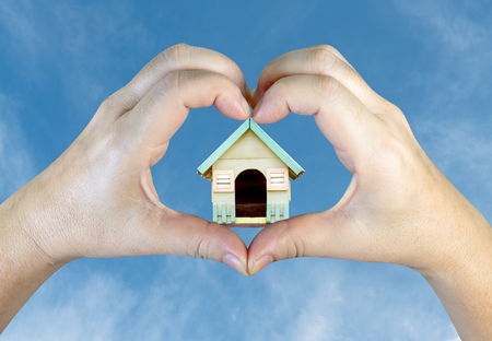 person hands making a heart shape with wooden house on sky background Stock Photo