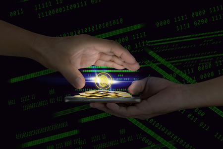 Human hand holding mobile smart phone with piles of golden coins and bitcoin symbol on binary background Stock Photo