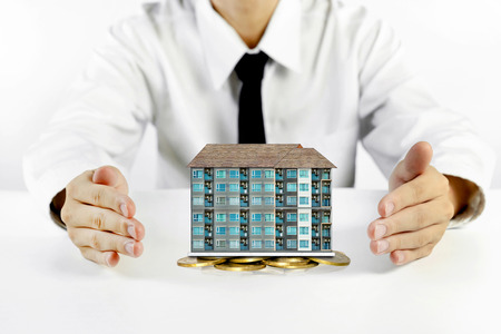 businessman hands protecting condominium model with piles of golden coins