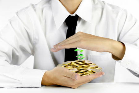 businessman hands protecting piles of golden coins,Lucky economic growth concept