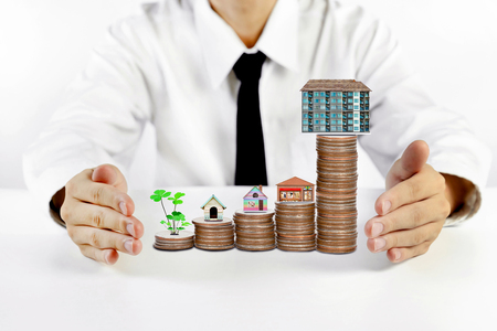 businessman hands protecting house model with piles of coins Stock Photo