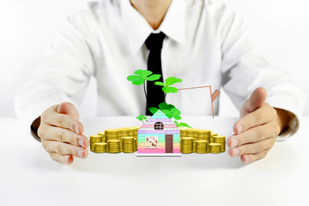 businessman hands protecting house model with piles of golden coins Stock Photo
