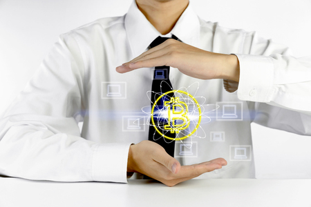 businessman hands protecting bitcoin symbol with laptop icons Stock Photo