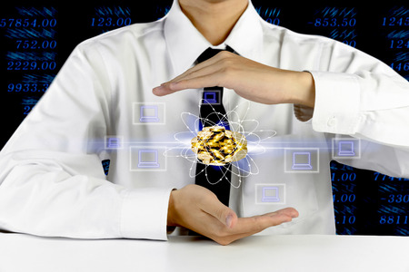 businessman hands protecting piles of golden coins with laptop icons Stock Photo