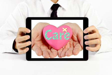 Businessman holding a tablet with heart and write the word care