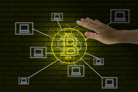 Hand touched with bitcoin symbol and laptop icons on brick wall background
