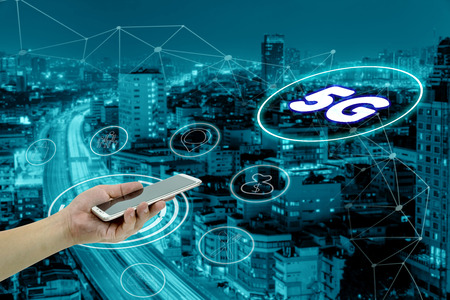 hand holding mobile smart phone with cityscape,5G network interface and icon concept