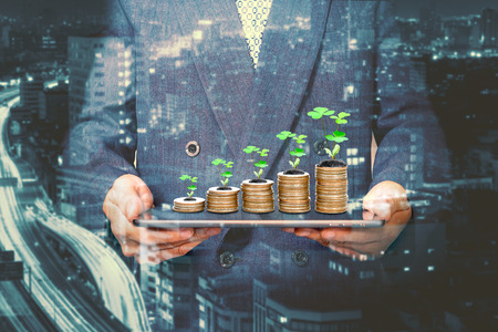 Geschäftsmann, der eine Tablette mit Münzstapel und Baum hält, glückliches Wirtschaftswachstumskonzept