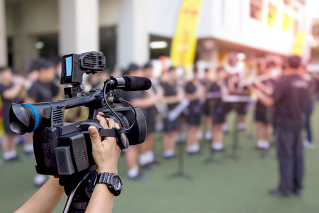 hand holding a video camera with marching band blurred background