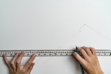hand holding ruler and clutch-type pencil with canvas background Stock Photo