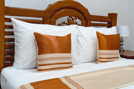 Brown pillows on wooden bed Banque d'images