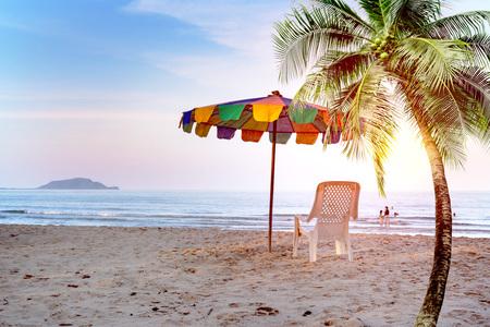 White beach chair and umbrella on tropical beach with orange sky Stock Photo - 118116781
