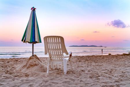 White beach chair and umbrella on tropical beach with orange sky Stock Photo - 118116783