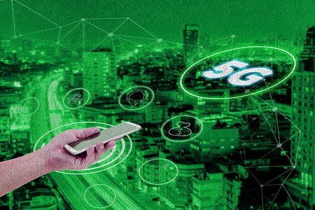 Abstract green oil paint with 5G network interface and icon concept,hand holding mobile smart phone with cityscape textured background