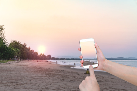 hand holding mobile smart phone with front the beach and sky  background