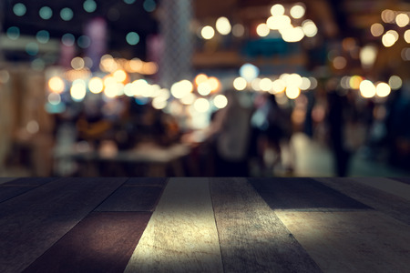 top desk with blur restaurant background,Wooden table and blurred bokeh of night street background Stock Photo