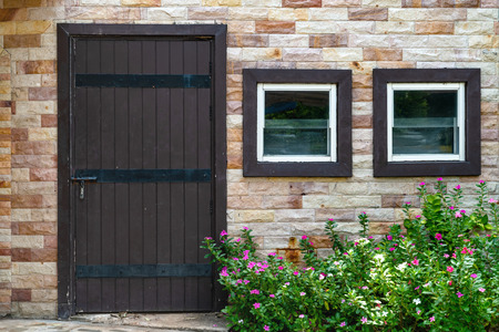 brown wooden door and window with brick wall background