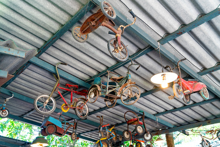 Ancient bicycles for children hanging on the roof