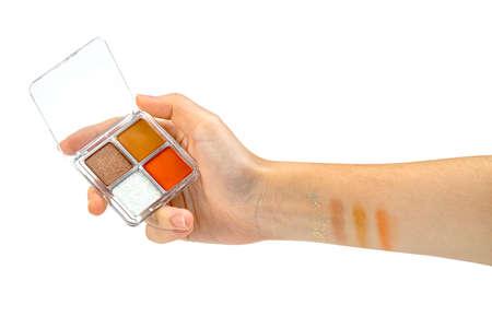 Hand holding eye shadow isolated on white background