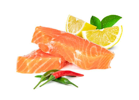 Piece of fresh salmon fillet sliced with lemon and chili isolated on white background Standard-Bild