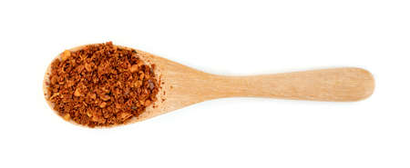 red ground paprika powder or dry chili pepper with wooden spoon isolated on white background
