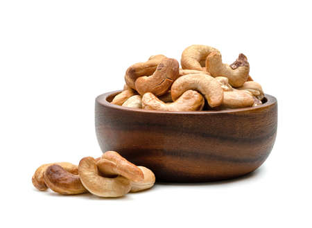 Roasted cashew nuts in wooden bowl isolated on white background