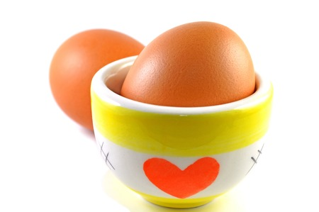 Eggs and ceramic cup on white background photo