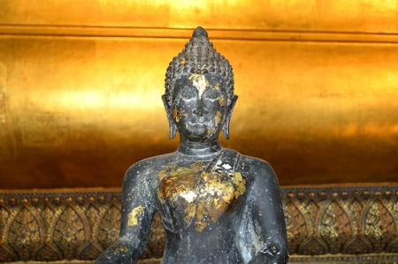subduing: Seated buddha image in the attitude of subduing Mara at Wat Pho Bangkok Thailand