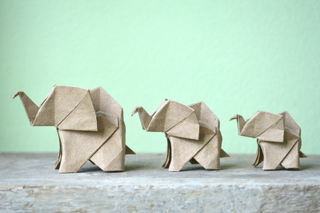 Brown origami elephant on green background