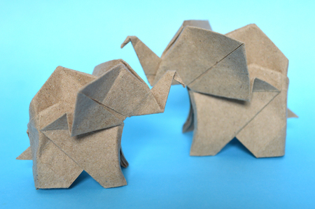 Brown origami elephant on blue background