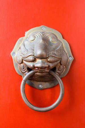 lion knocker on the chinese traditional red door of temple in Bangkok