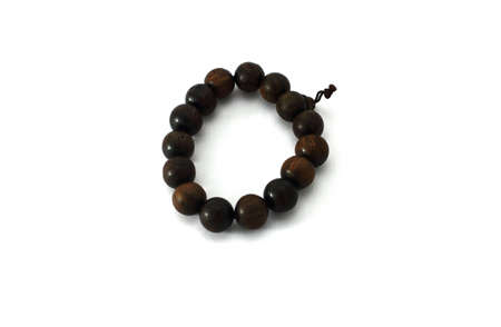 The black necklace is made of carved wood