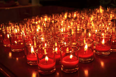Many red votive candles light the darkness in church  Stock Photo