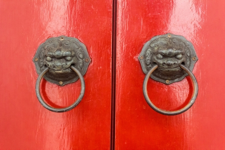 lion knocker on the chinese traditional red door of temple