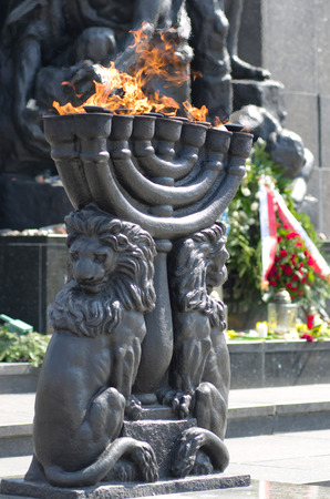rising dead: Warsaw Ghetto Monument - Menorah with burning flame Stock Photo