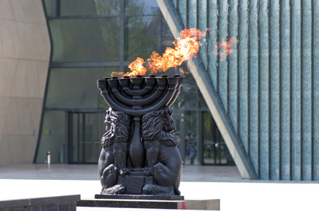Warsaw Ghetto Monument - Menorah with burning flame photo