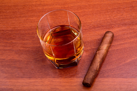 Whiskey and cigar on the wooden table photo