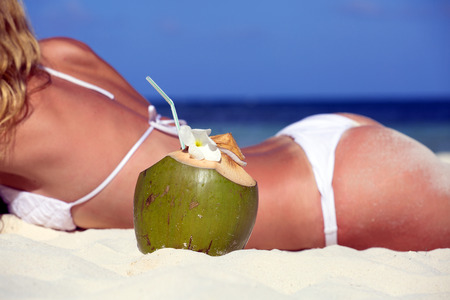 Coconut on the background of the girls on the beach photo