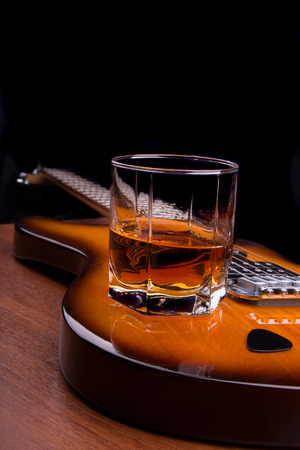 Glass of rum and plectrum on the electric guitar Banco de Imagens