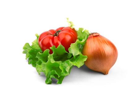 tomato and onion lie on a salad leaf on a  white background photo