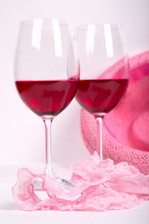 pink panties: two glasses of red wine on a white background near pink panties and hat