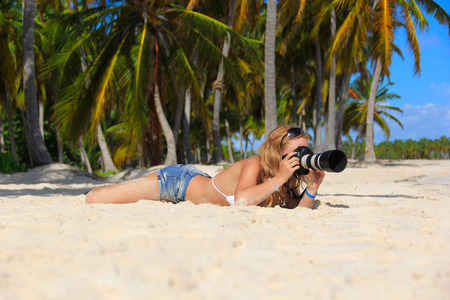 girl on the Caribbean beach with a camera photo