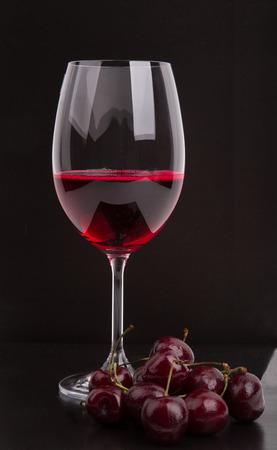 Glas Rotwein in der Nähe der Kirsche auf einem schwarzen Hintergrund Standard-Bild - 30448949