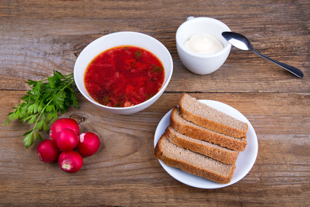 white Bowl of soup - borsch with parsley radish and bread photo