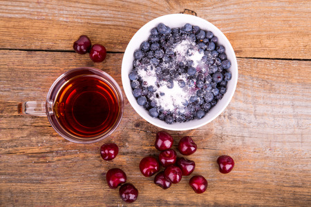 black cherry: cup of tea sweet cherry and blueberry in white bowl on a wooden background