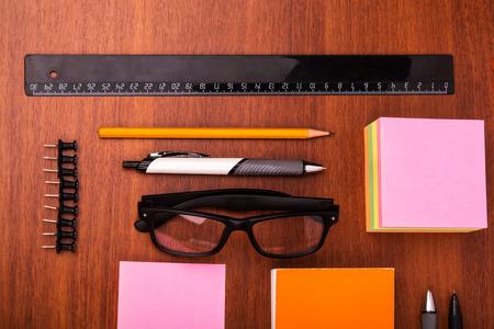 articulos de oficina: Escritorio de oficina con regla gafas pluma lápiz y otros artículos de oficina Foto de archivo