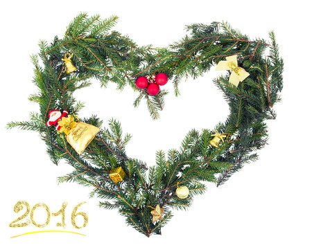 Christmas frame from fir branch shape of a heart with yellow decorations.retro toning