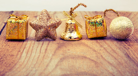 Christmas gold toy on old wooden background.retro toning Banco de Imagens